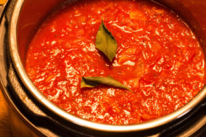 Lastly, adding the bay leaves into the tomato soup base.
