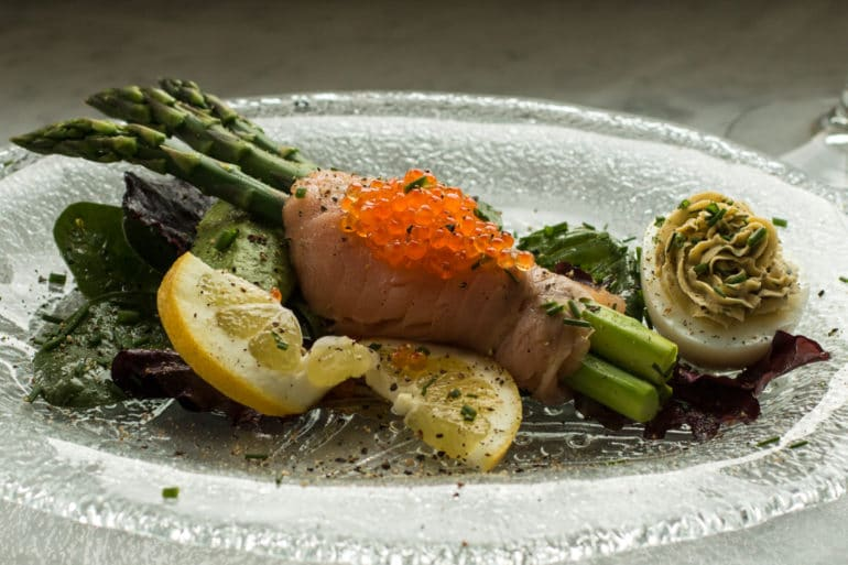 Plated asparagus wrapped in cold smoked salmon with a smoked salmon deviled egg.