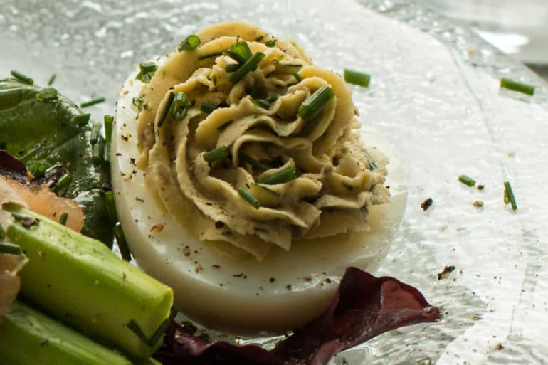 "A ""Smoked Salmon Deviled Egg"", garnished with finely snipped chives."