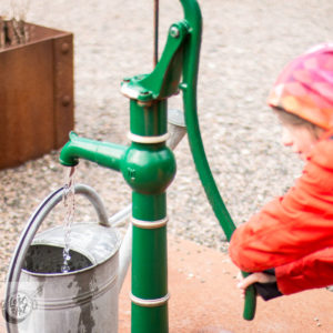 An Easter witch (small child) punping water from a hand pump.