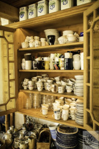 Plates, saucers, cups and glasses in an antique Buffet/Crockery Cabinet.
